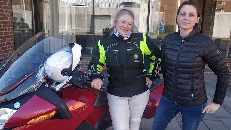 Två kvinnor vid en motorcykel.