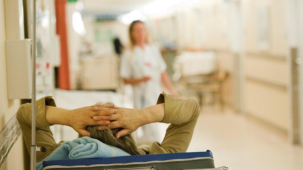 Äldre patient i en säng i en sjukhuskorridor.