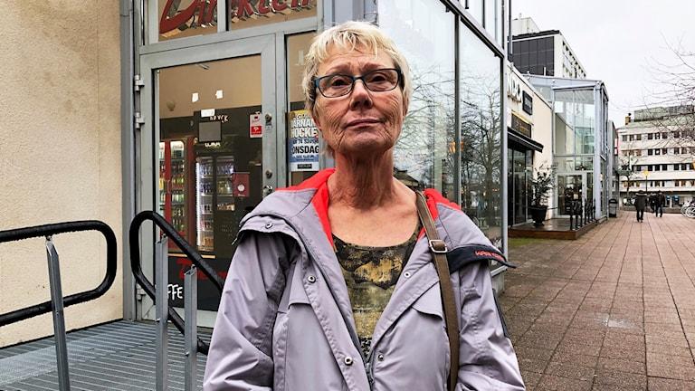 Äldre kvinna framför gallerian Flanaden i Värnamo.