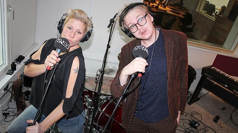 Sanna och Malte står framför ett trumset och sjunger i mikrofoner.