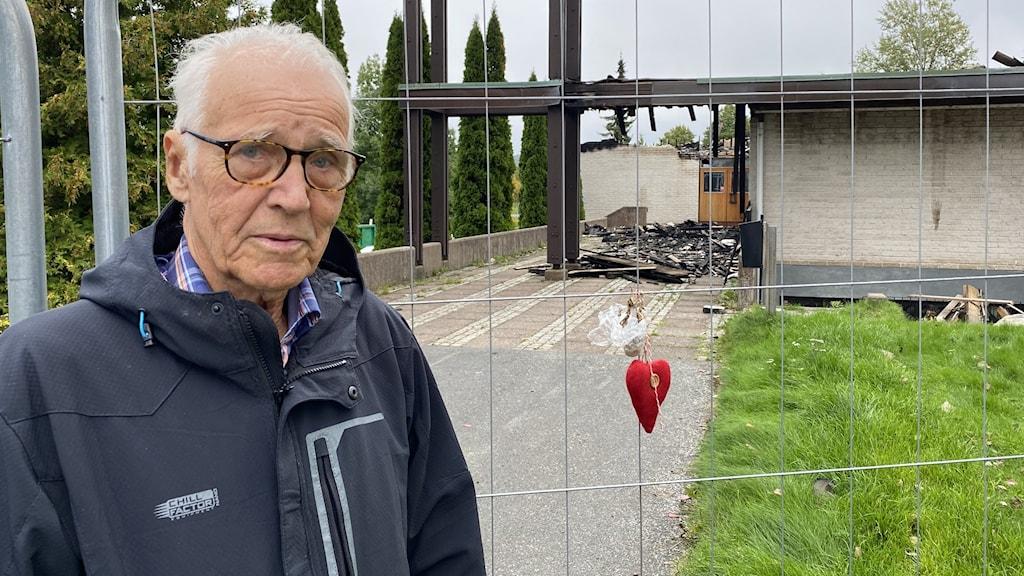En äldre man står framför en nedbrunnen kyrka
