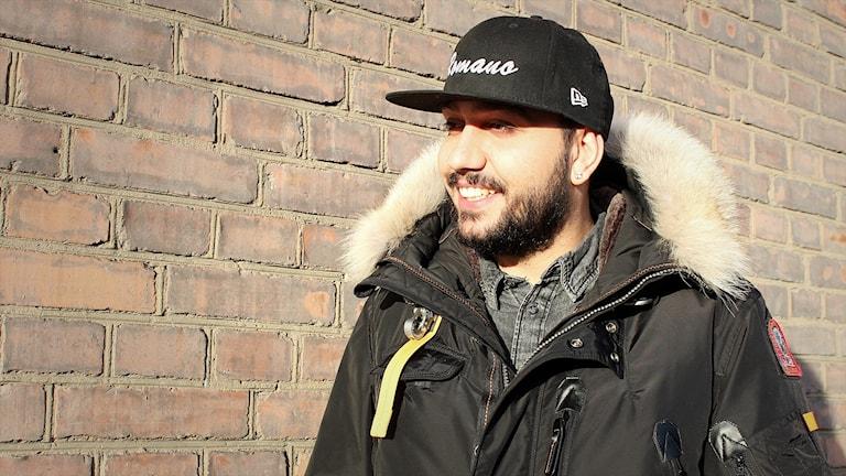 Alil Ajrulovic framför en tegelvägg.