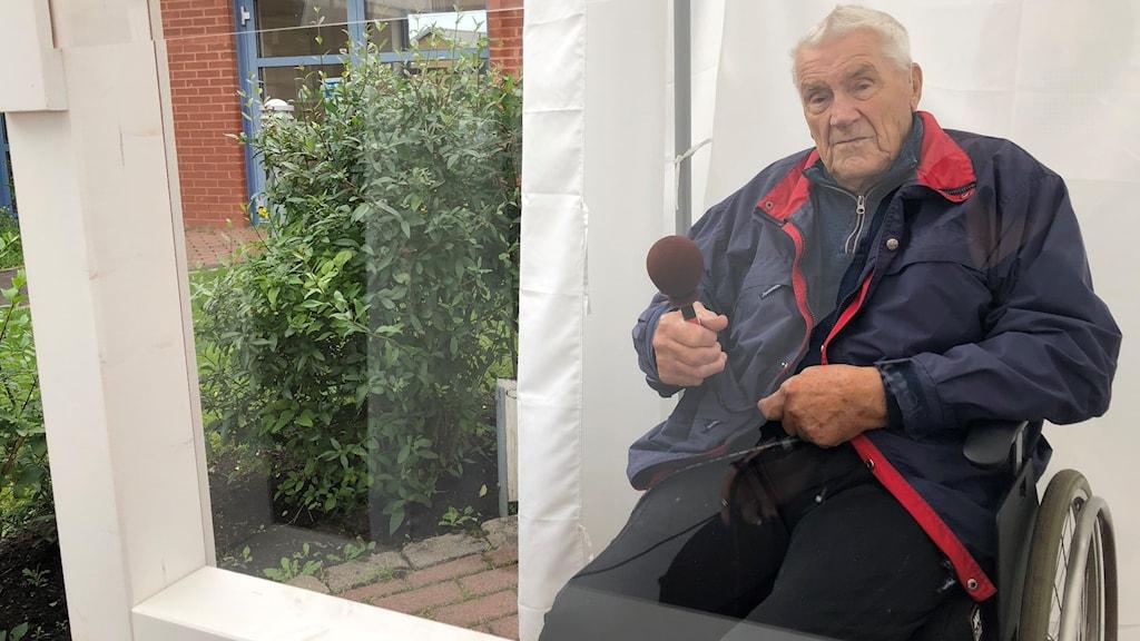 Nils Petersson sitter i en rullstol utomhus bakom en plastvägg.