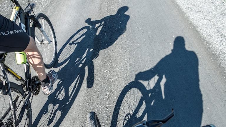 Skuggan av två personer som cyklar.