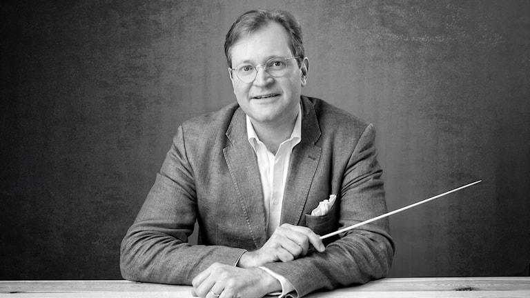 Christian von Gehren sitter med en dirigentpinne i ena handen.