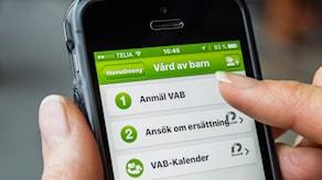 """Närbild på en smartphone där det står """"anmäl VAB"""" på skärmen."""