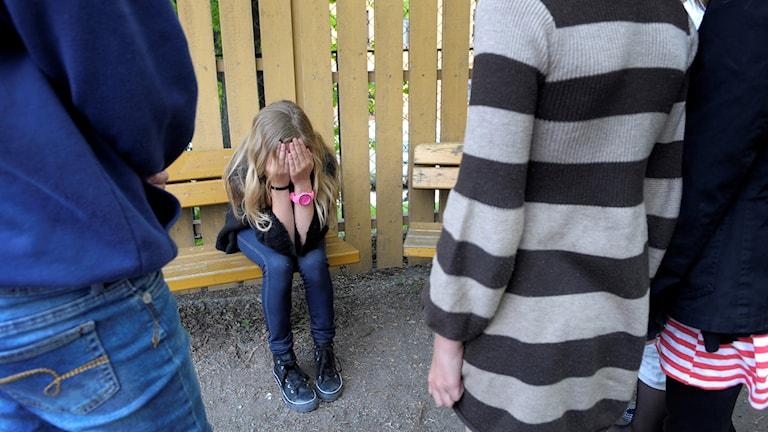 En flicka mobbas av flera personer som syns i förgrunden.