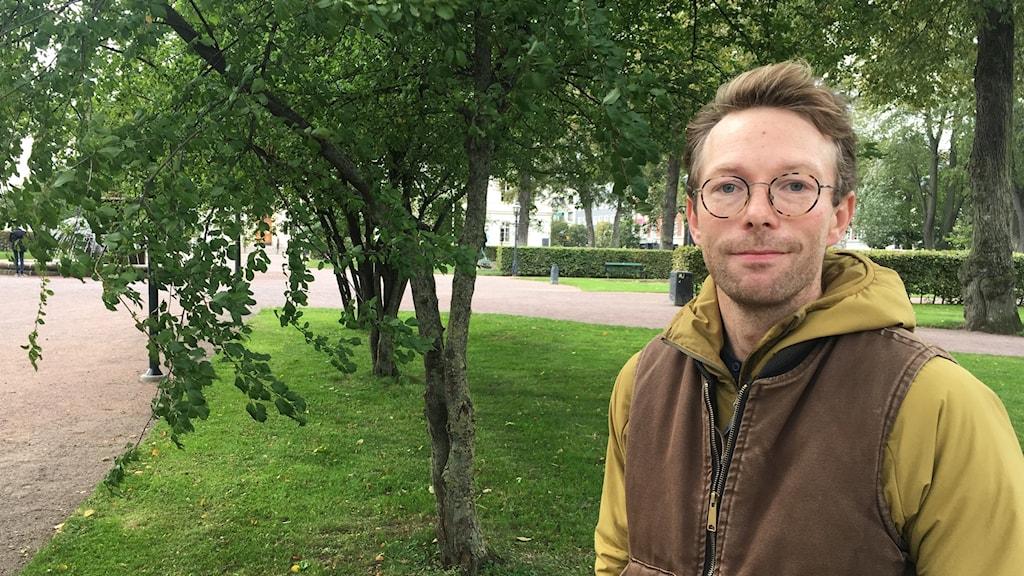 Simon Jonegård framför ett lövträd.