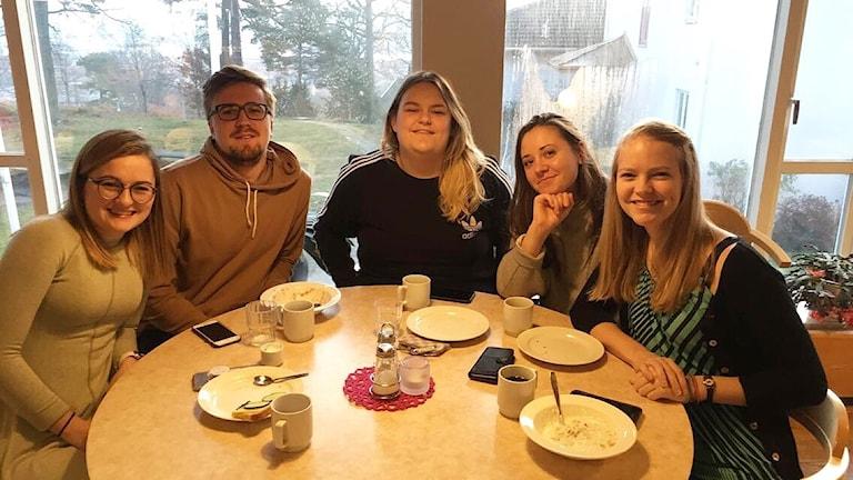Fem studenter på Södra Vätterbygdens folkhögskola sitter samlade kring ett bord i en matsal.