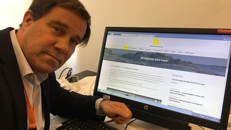 Martin Wannholt, kommunalråd och partiledare för Demokraterna i Göteborg, sitter vid sin dator där Demokraterna i Göteborgs hemsida syns. Foto: Oskar Mattisson/Sveriges Radio.