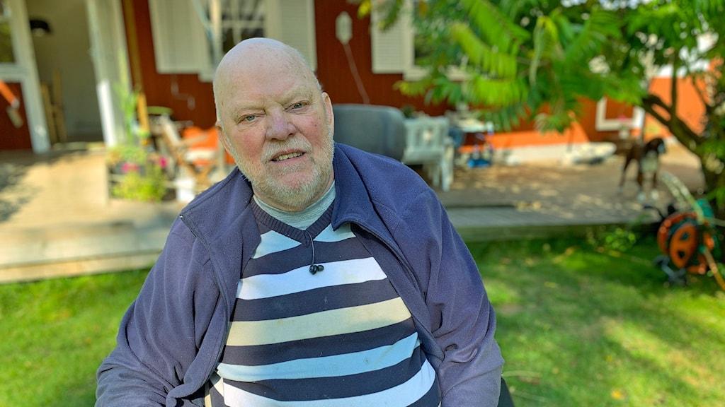 Stig Westerberg i sitter i en rullstol i sin trädgård i Furusjö.
