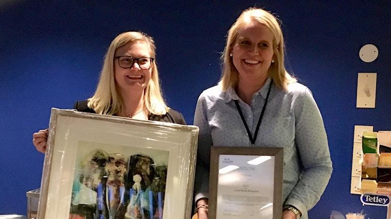 Jenny Petersson och Linda-Marie Rönnqvist håller i en tavla respektive ett diplom.