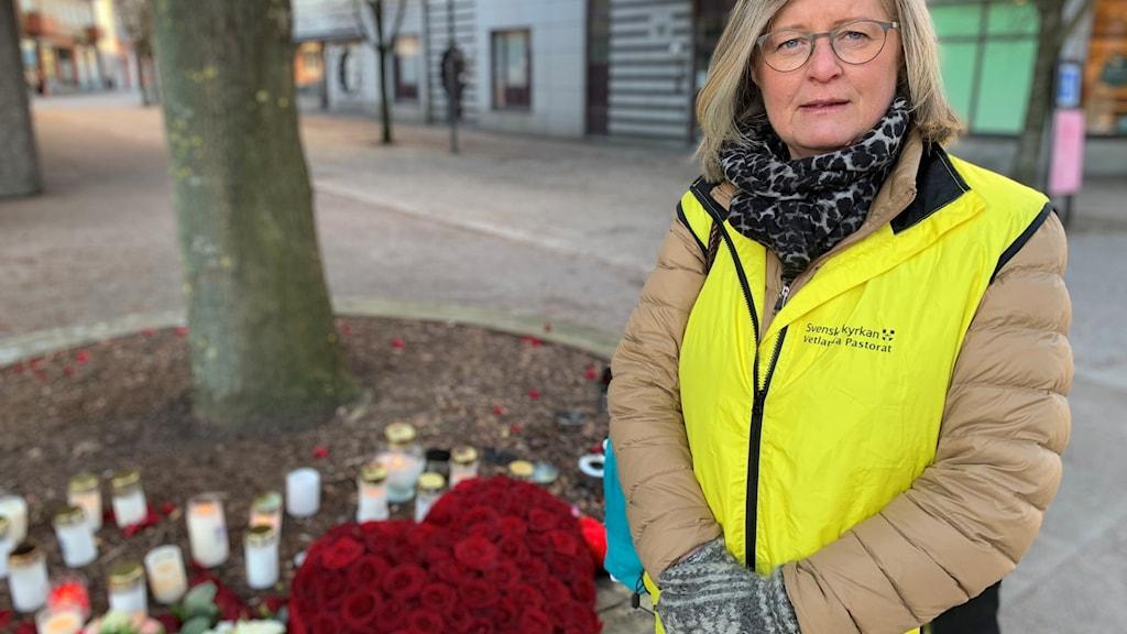 Kvinna står framför stearinljus och blommor.
