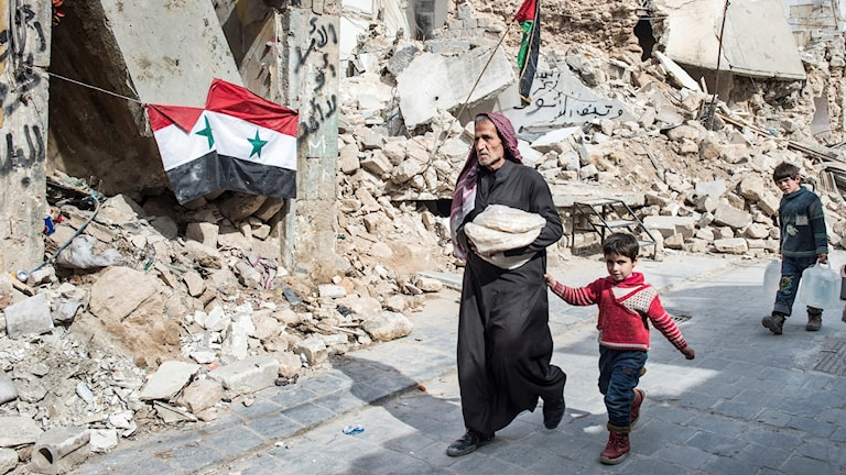 En man och en pojke går bland rasmassorna efter sönderbombade hus.