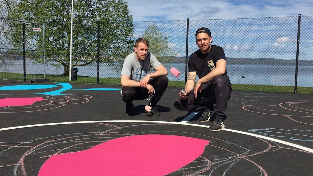 Gatukonstnären Victor Egerbo, till höger i bild, målar basketplanen på vid Vätterstranden på penseln på uppdrag av Jönköpings kommun.
