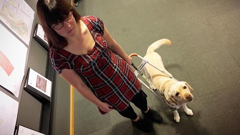 """Kvinna med mörkt axellångt hår och röd klänning med mörkare rutmönster, svarta byxor och svarta skor står på grått golv i inomhusmiljö. I ena handen håller hon kopplet till en gul labrador retriever-hund med viftande svans. Hunden tittar upp i kameran. Det finns en skylt på kopplet där det står """"Stör ej. Ledarhund""""."""