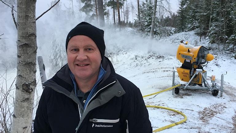 Lars-Åke Bertilsson, Hallby, framför en snökanon som sprutar ut snö.