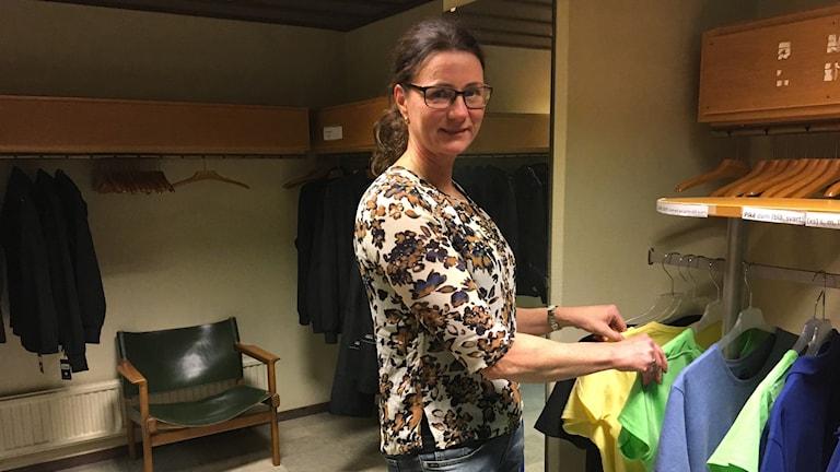 Helén Gustafsson tittar bland upphängda tröjor i olika färger.