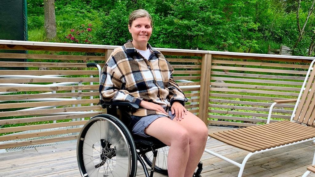 Kvinna sitter i en rullstol på en altan.