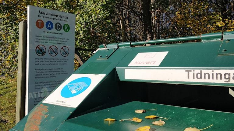 En container och en informationsskylt vid en återvinningscentral.