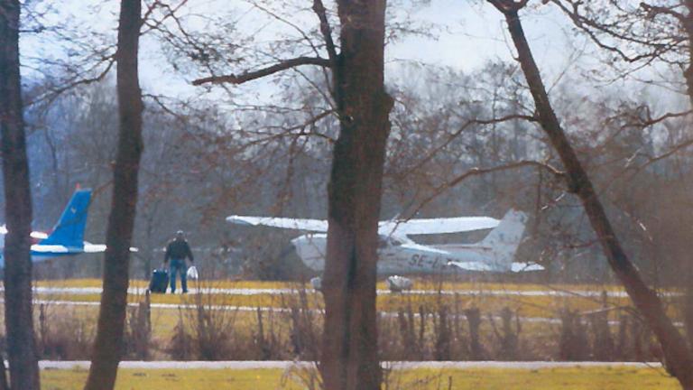 En man med resväska går mot ett flygplan.