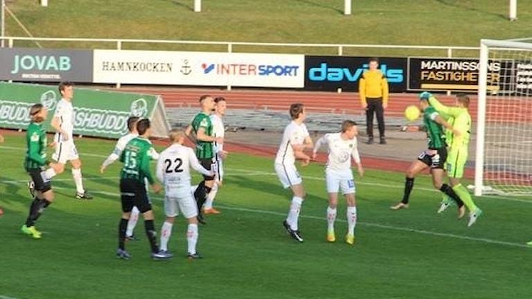 Spelare i vitt och grönt på en fotbollsplan