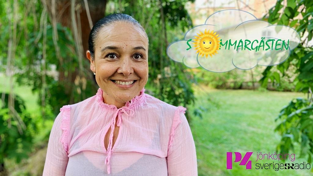 En kvinna i rosa står i en grön trädgård