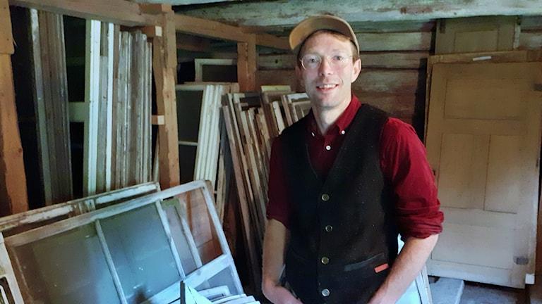 En man i keps står i ett rum fullt med söndriga fönster