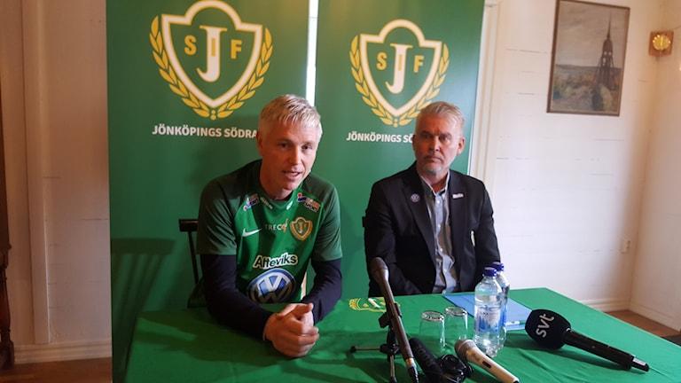 Jörgen Wålemark i en grön J-Södratröja vid ett bord på presskonferensen.