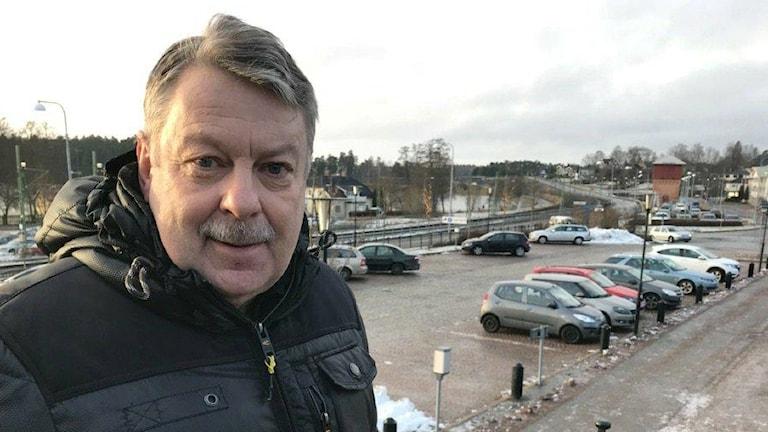Mullsjös kommunchef Lennie Johansson står på en trappa ovanför en parkeringsplats.