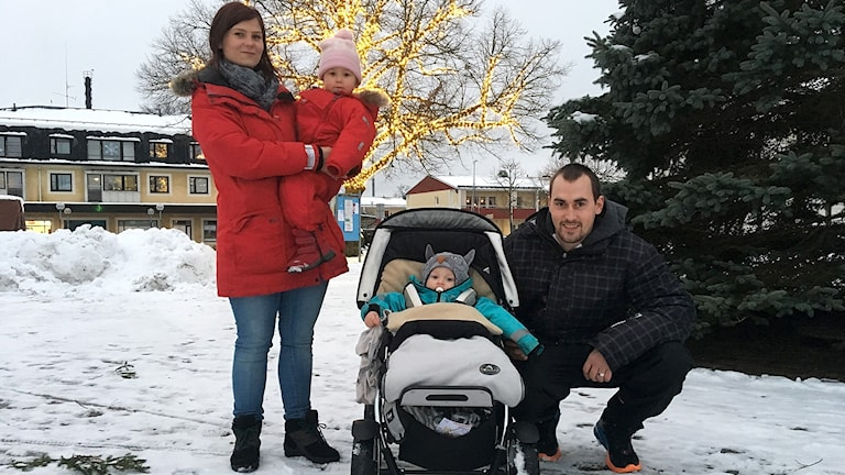 Amanda håller ett barn i famnen, Mattias sitter på huk bredvid en barnvagn med ett barn i.