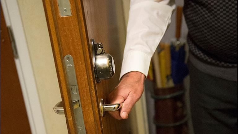 En äldre person öppnar dörren till sin lägenhet.