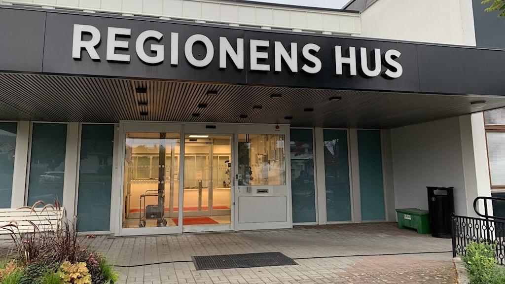 """Entrén till Regionens hus i Jönköping. Glasdörrar med svart tak ovanför där det står """"Regionens hus"""" i vita bokstäver."""