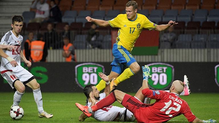 Viktor Claesson i landslagsdräkt hoppar över två motspelare som ligger ner på fotbollsplanen.