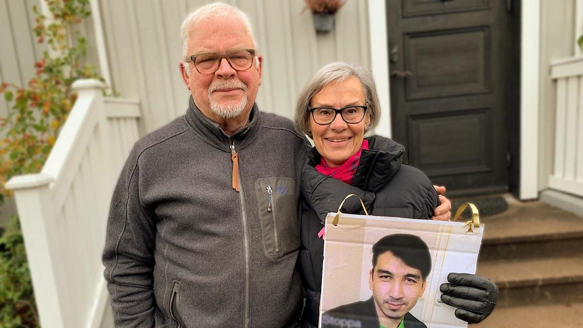 Magnus och Eva Britt Apelqvist står utanför sitt hus, håller upp en bild på Nasrullah.