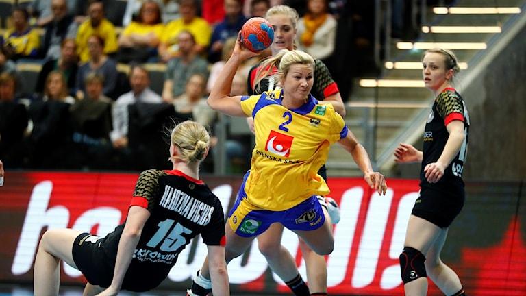 Ulrika Toft Hansen, klädd i Sveriges landslagsdräkt, är mitt i ett hopp och ska precis iväg kasta bollen mot mål.