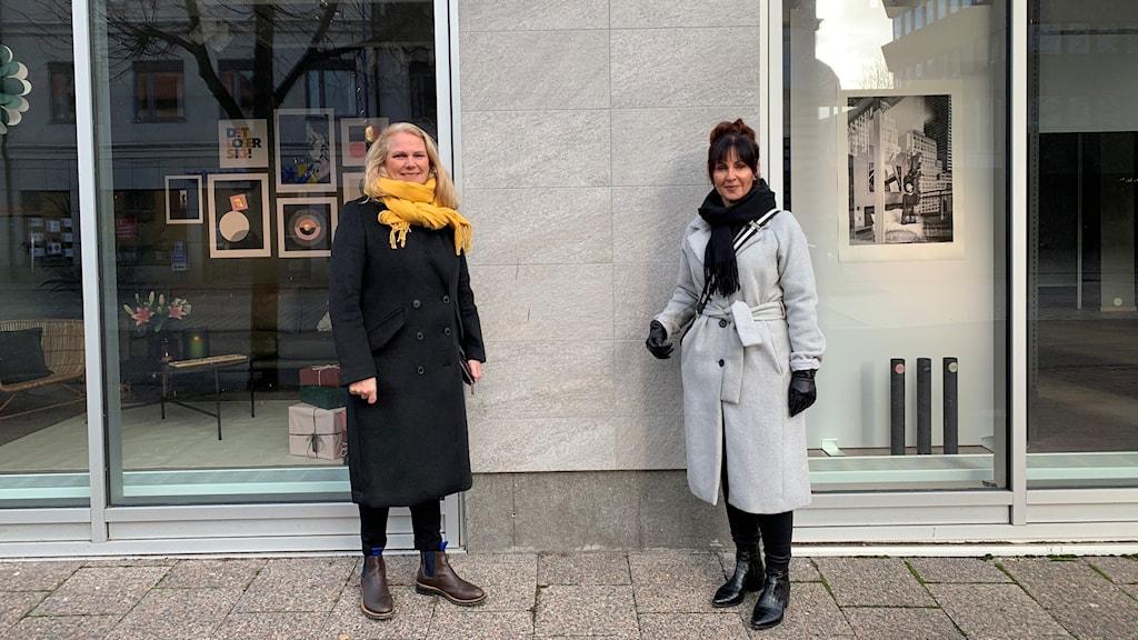 Två kvinnor står utanför ett skyltförnster.