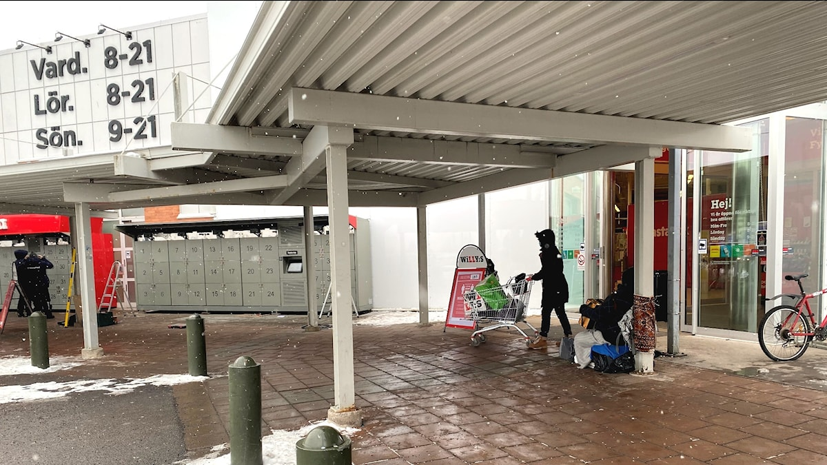 En kvinna kör ut en kundvagn ur butiken och en man spelar dragspel.
