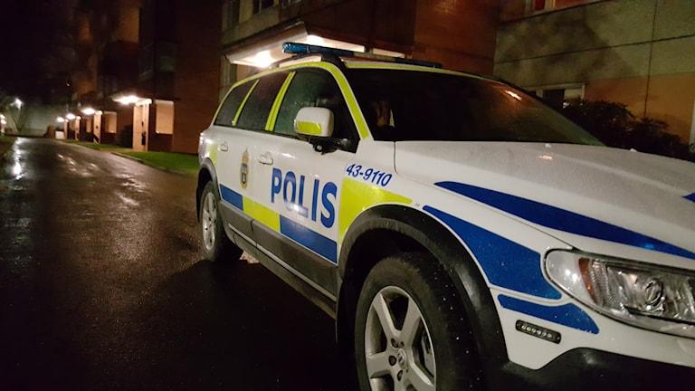 Polisbil utanför hyreshus.