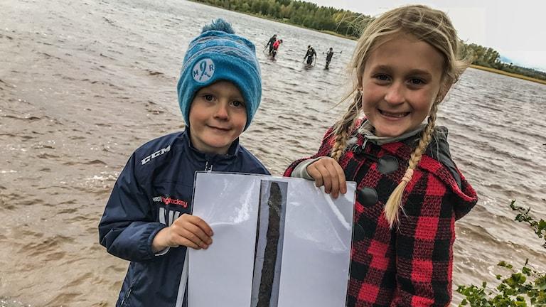 Saga och hennes bror Vilgot står framför sjön Vidöstern och visar upp en bild på svärdet.