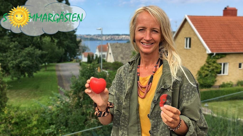 Cajsa Tengblad står framför några hus, håller i en godisbit och ett hjärta.
