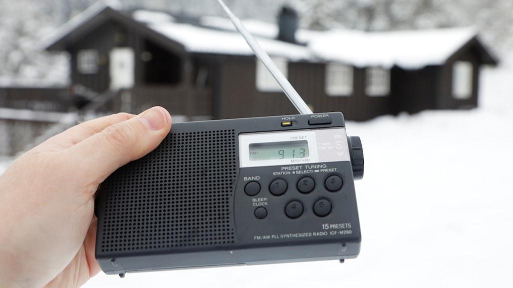 En person håller i en svart radioapparat.