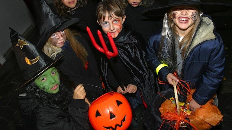 Utklädda barn har korgar och behållare att samla godis i.