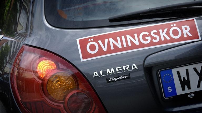 Röd övningskörningsskylt på grå bil.
