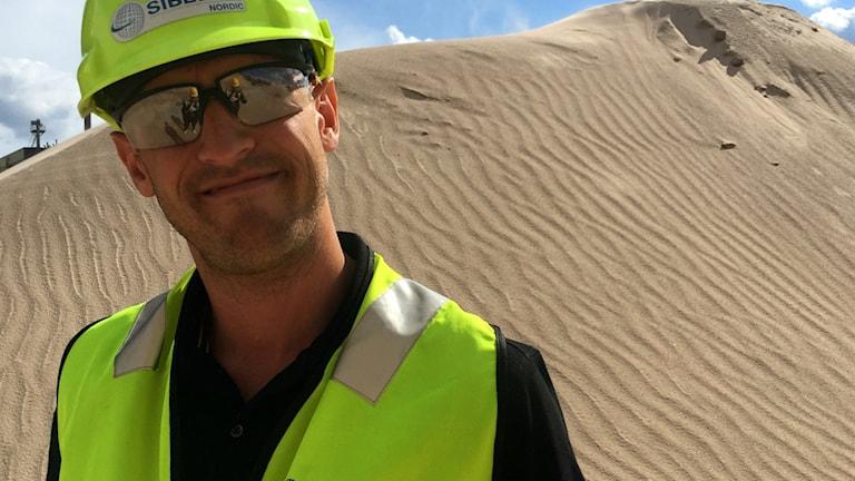 Platschef Erik Hallman står framför en sandhög.