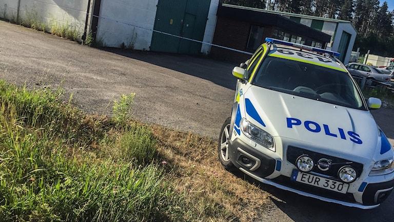 En polisbil framför ett avspärrat område.