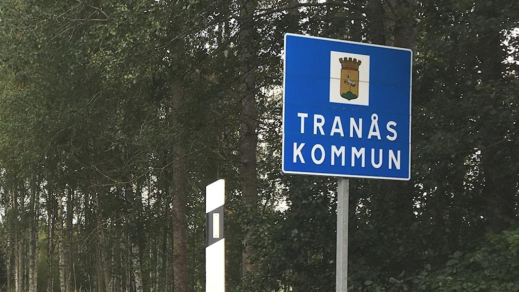 Skylt som det står Tranås kommun på. Bredvid en asfalterad väg.