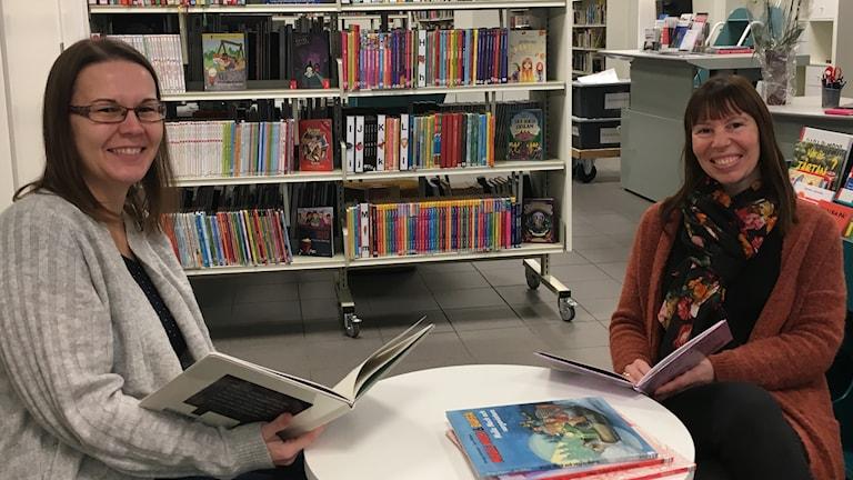 Två kvinnor sitter vid ett lågt barnbord och läser barnböcker på ett bibliotek.