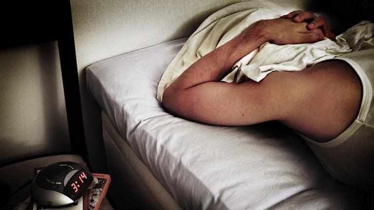En person ligger i sängen med en kudde över huvudet.