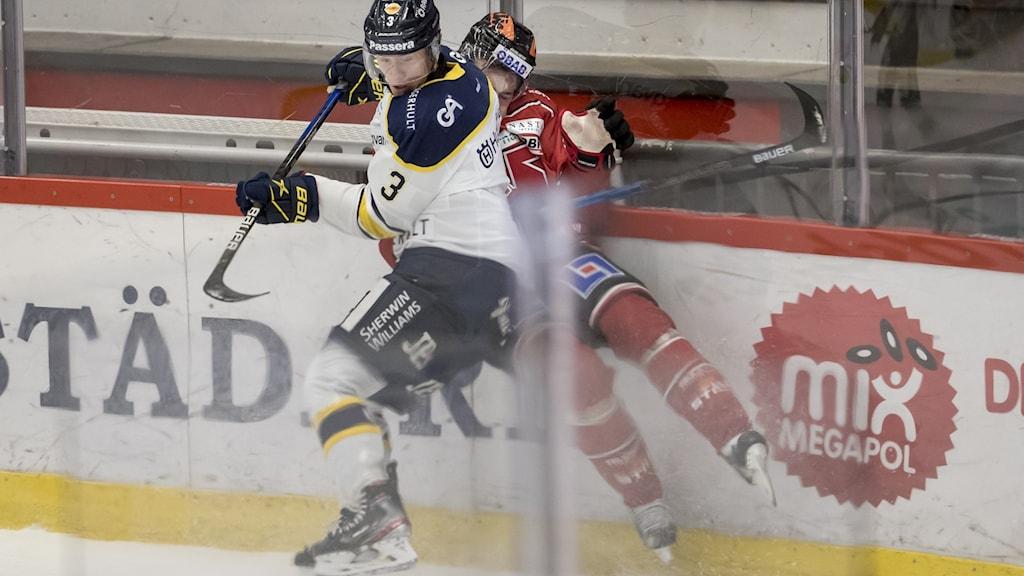 Spelare i HV71 tacklar spelare i Örebro.